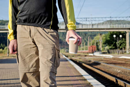 Young man in sport tourist clothes stay on the platform of the station, near the rails, and holds cup of coffee Stok Fotoğraf