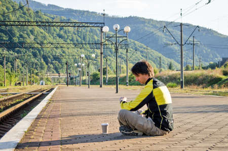 Young man in tourist clothes sits on platform of station, he looks at watch while waiting for train, near rails, with cup of coffee Stok Fotoğraf