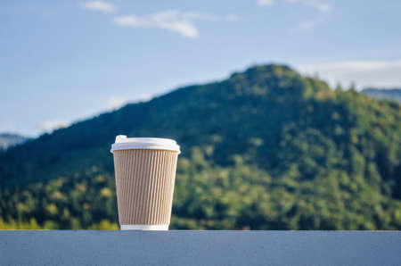 Brown disposable cup of coffee on the background of green carpathian mountains and blue sky Stok Fotoğraf