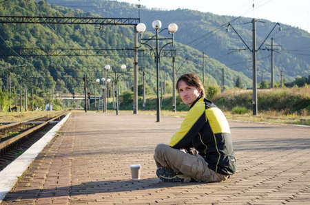 Young man in sport tourist clothes sits on the platform of the station, near the rails, and holds cup of coffee