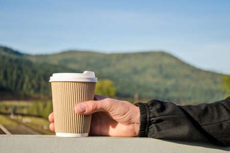Man hand holds a brown disposable cup of coffee on a background of green carpathian mountains and blue sky Stok Fotoğraf