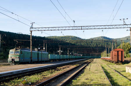 Railway tracks and wagons of the station against the background of the high Carpathian mountains Stok Fotoğraf