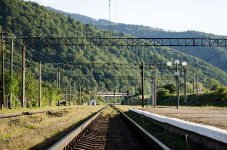 Railway tracks and platform of the station against the background of the high Carpathian mountains