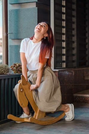 Young happy european brown hair girl sitting on a wooden toy horse and laughing