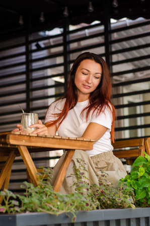 Young happy european girl with brown hair sits in the summer at a wooden table with a glass of latte, on a street area of a cafe with a beautiful striped background and flowers