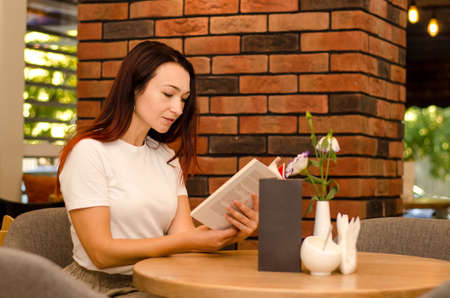 Young happy european girl with brown hair sitting in a cafe near a brick wall reading a book at the table