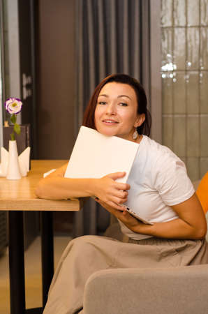Young, happy, tired european girl with brown hair sits in a light cafe at a wooden table with a flower, hugging a white laptop Stok Fotoğraf
