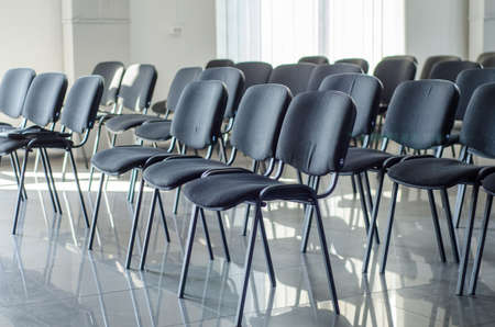 Empty soft black chairs in a large empty conference room, empty large room with no people Stok Fotoğraf