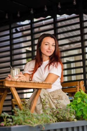 Young happy caucasian woman with brown hair sits at wooden table with glass of latte, on a terrace of cafe with beautiful striped background and flowers in summer Stok Fotoğraf