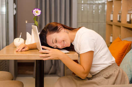 Young, happy, tired caucasian woman with brown hair sits in a light cafe at a wooden table with a flower, lying on a white laptop
