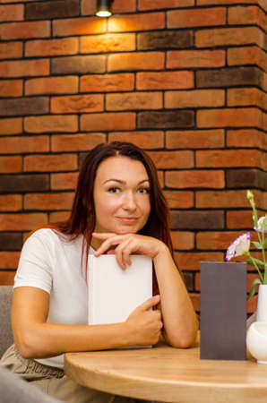 Young happy caucasian woman with brown hair sitting in a cafe near a brick wall with book at the table
