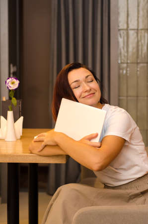 Young, happy, tired caucasian woman with brown hair sits in a light cafe at a wooden table with a flower, hugging a white laptop Stok Fotoğraf