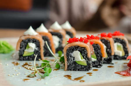 Set of rolls of black rice, fish and philadelphia cream cheese, sesame seeds, on a white plate, poured with unagi sauce and microgreen sprouts, side view