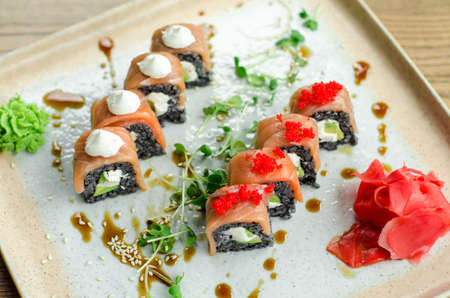 Set of rolls of black rice, fish and philadelphia cream cheese, sesame seeds, on a white plate, poured with unagi sauce and microgreen sprouts, top view Stok Fotoğraf