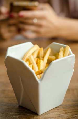 Fries are served at the restaurant in a in white porcelain box styled like take away box. On a wooden table on the background of female hands with a phone on lunch
