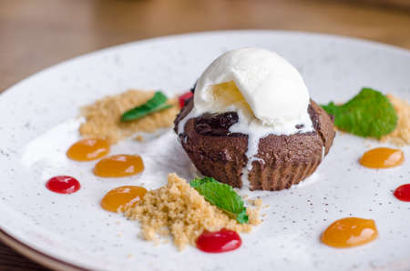 Delicious sweet chocolate fondant with drops of colorful jam and a scoop of melted ice cream, on a white plate in a cafe Stok Fotoğraf