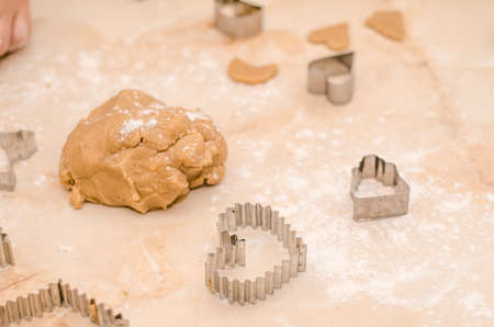 Raw dough and cookie cutters, on the table while making Christmas gingerbread cookies in the shape of heart