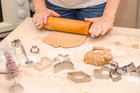 Female hands prepare festive gingerbread cookies for christmas, she rolled out dough and cut cookies with a cookie cutters Stok Fotoğraf