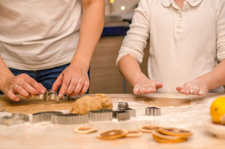 Hands of mother and daughter prepare festive gingerbread cookies for christmas, they roll out the dough and cut the cookies with cookie cutters Stok Fotoğraf