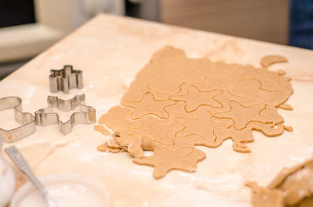 Raw dough and cookie cutters, on the table while making Christmas gingerbread cookies in the shape of a snowflake, boot Stok Fotoğraf