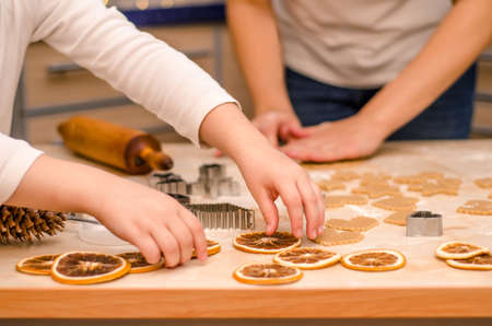 Hands of mother and daughter prepare festive gingerbread cookies for christmas, girl decorates the table with dry oranges
