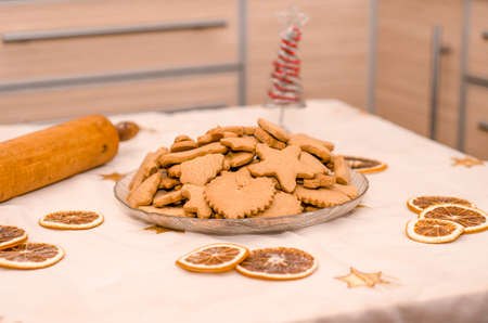 Festive Christmas still life in the kitchen, gingerbread cookie, rolling pin, garland lights, oranges, Christmas decorative tree Stok Fotoğraf