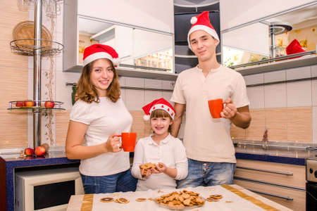 Happy family in Christmas red hats, drinking tea in kitchen, daughter holding a lot of gingerbread cookies that they have prepared