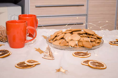 Festive Christmas still life in the kitchen, gingerbread cookie, rolling pin, garland lights, oranges Stok Fotoğraf