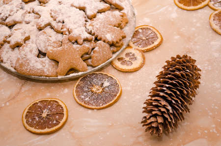 Festive Christmas still life in the kitchen, gingerbread cookies with powdered sugar, dried oranges, christmas cone, cinnamon stick