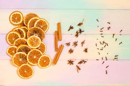 Set for mulled wine on a rainbow background, scattered dry oranges, cinnamon, cloves, star anise, with copyspace Stok Fotoğraf