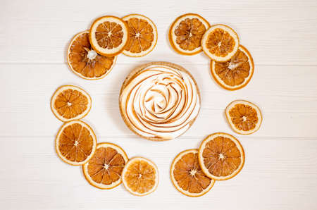 Delicious sweet orange tart with a baked top, white background with slices of dry fruit in shape of circle, as a background for holiday menus and posts Stok Fotoğraf