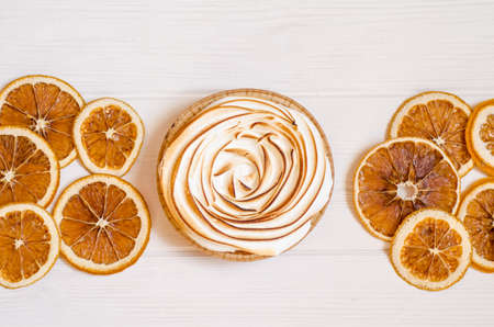Delicious sweet orange tart with a baked top, white background with slices of dry fruit, as a background for holiday menus and posts