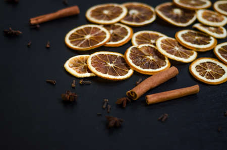 Set for mulled wine on a black background, scattered dry oranges, cinnamon, cloves, star anise, with copyspace