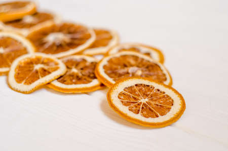 Dried orange slices are scattered on a white wooden table, a beautiful background for postcards and New Year posts