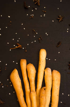 Ruddy grissini, dry long bread with sesame seeds, on a black background with spices, star anise and cloves, with copyspace