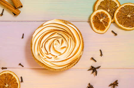 Delicious sweet orange tart with a baked top, and a rainbow background with spices, cinnamon, star anise, cloves, as a background for holiday menus and posts Stok Fotoğraf