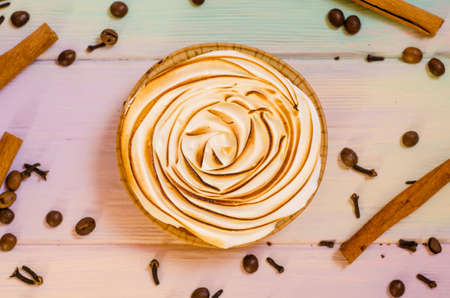 Delicious sweet orange tart with a baked top, and a rainbow background with spices, cinnamon, coffee, star anise, cloves, as a background for holiday menus and posts