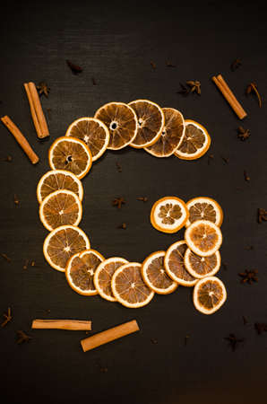 Set for mulled wine on a black background, in form of letter G, scattered dry oranges, cinnamon, cloves, star anise, with copyspace