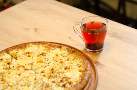 Delicious wet fresh pizza on a cafe table next to a cup of fruit red tea on a wooden table, top view Stok Fotoğraf