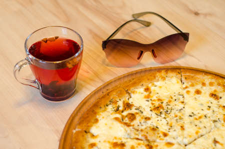 Delicious wet fresh pizza on a cafe table next to a cup of fruit red tea on a wooden table, sunglasses lie next to it Stok Fotoğraf