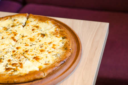 Delicious wet fresh pizza on a cafe table on a wooden table, against the background of a burgundy sofa with copyspace