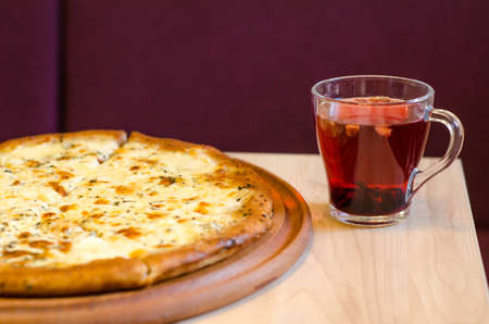 Delicious wet fresh pizza on a cafe table next to a cup of fruit red tea on a wooden table, against the background of a burgundy sofa