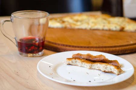 Leftovers of pizza dough and red tea on a table in a cafe, food ending concept, cancellation of a cafe visit Stok Fotoğraf
