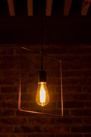 Metal chandelier with retro orange incandescent lamp in a restaurant against brick wall background Stok Fotoğraf