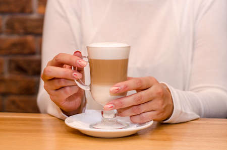 Young woman in a cafe drinks a latte, holds a transparent glass with her hand on a white saucer. Waits for the coffee to cool. With copyspace Stok Fotoğraf