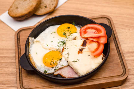 Hearty breakfast is served in a black frying pan and wooden board, fried eggs with bacon and tomatoes, two pieces of bread are on a wooden table