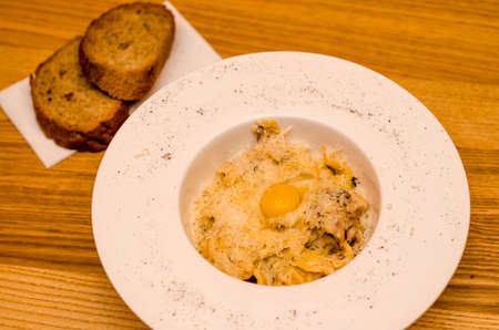 Appetizing carbonara pasta with egg yolk on a white plate in a restaurant, two pieces of bread lie on a wooden table