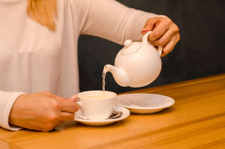 Young woman in a cafe drinks ginger tea and pours it from a teapot into a white cup on a saucer Stok Fotoğraf