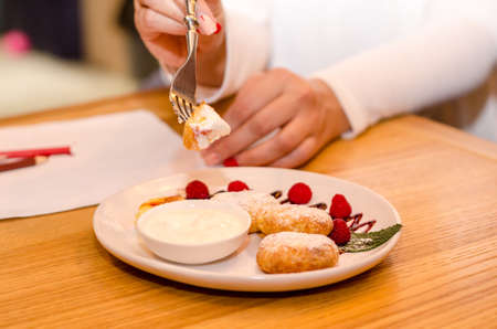 Young woman in a cafe eating cheese pancakes with raspberries and sour cream with a fork
