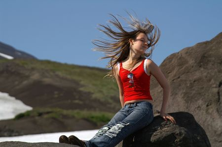 The warm wind blows to the hairs of girl sitting on stone. Stock Photo - 2272562
